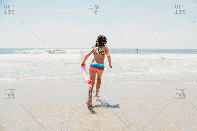 Girl wearing colorful bathing suit running with noodle at beach