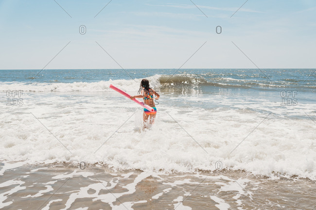 Girl wearing colorful bathing suit splashing in waves with noodle