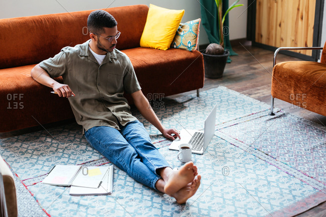 Young latin man sitting on floor working at home.