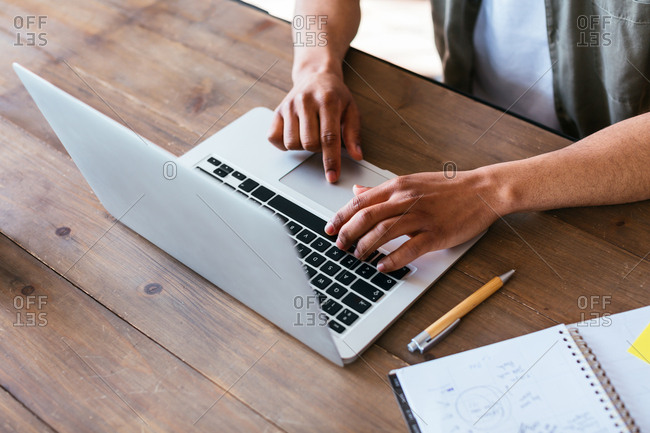 Anonymous man on wooden desk working with laptop.