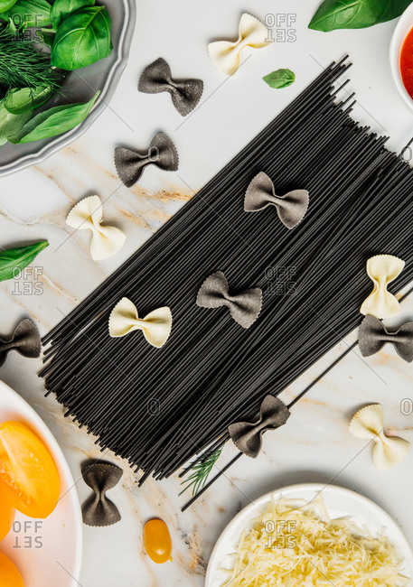 Squid ink black spaghetti with basil and cheese top view