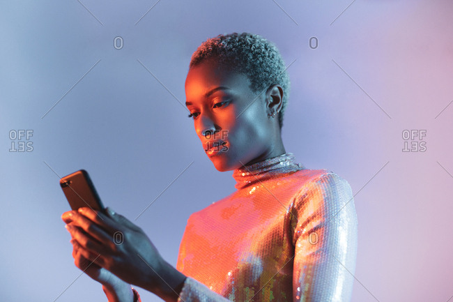 Creative shot of african american young adult female using smartphone