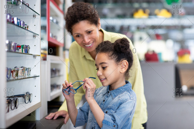 Young girl choosing glasses at the optician