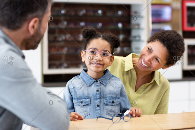 Young girl with new glasses at the opticians