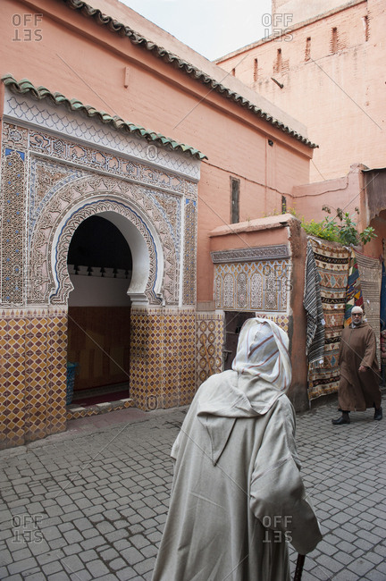 Marrakech, Morocco - January 22, 2013: Men in djellaba passing hamam in medina of marrakech
