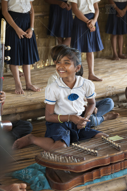 Cambodia - August 2, 2013: Smiling girl with stringed instrument in orphanage school cambodia