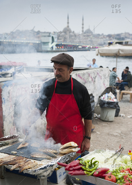 Istanbul - October 17, 2013: Man grilling fish for authentic turkish fish sandwich by galata bridge in istanbul