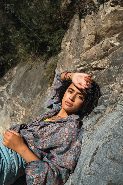 Beautiful and stylish African American female with afro hair lying on rocks and looking at camera