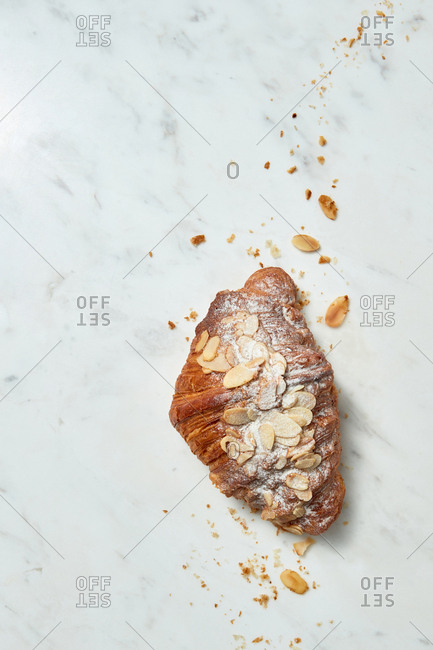 Delicious freshly baked French homemade croissant with almond crumbs on a gray marble background, copy space. Top view.