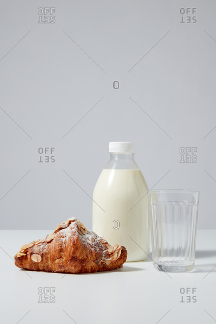 Bottle of organic milk with freshly baked homemade croissant covered in powdered sugar and almond chips on a light gray background. Place for text.