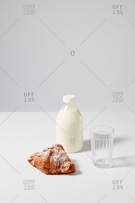 Breakfast set with freshly baked French homemade croissant with powdered sugar, bottle of natural organic milk and empty glass on a gray background. Copy space. Almond bakery.
