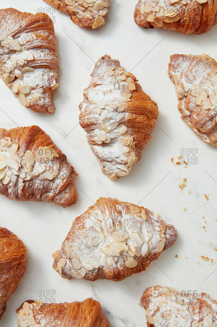 Sweet bakery pattern with homemade French croissants covered in powdered sugar and almond nuts on a marble background. Flat lay.