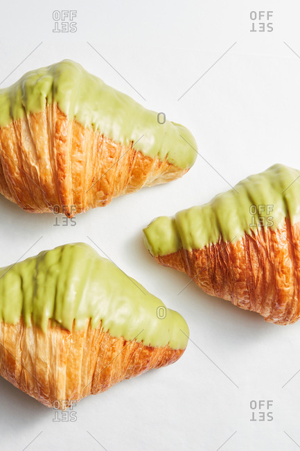 Delicious freshly baked homemade sweet glazed French croissants on a light gray background with copy space. Close up. Flat lay.