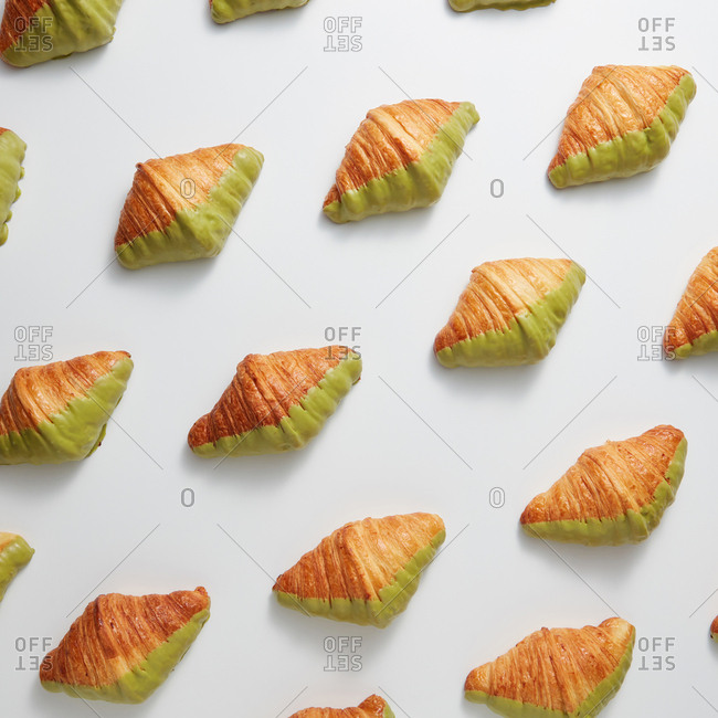 Gourmet pastry pattern from homemade croissants in a sweet green icing on a light gray background. Top view. Continental breakfast concept.