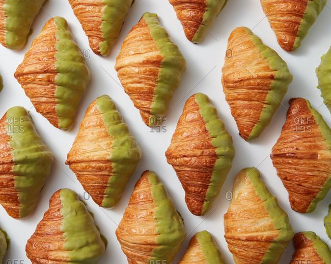 Rhombus background with freshly baked French homemade croissants with green sweet glaze on a light background. Flat lay.