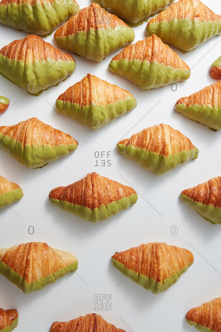 Fresh bakery pattern with French croissants covered in green glaze on a light gray background, copy space. Top view. Concept of breakfast continental.