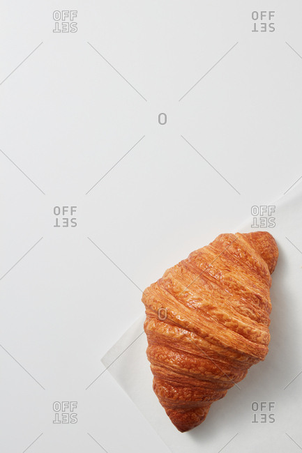 French homemade delicious croissant on a light gray background with copy space. Top view. Concept of continental breakfast.