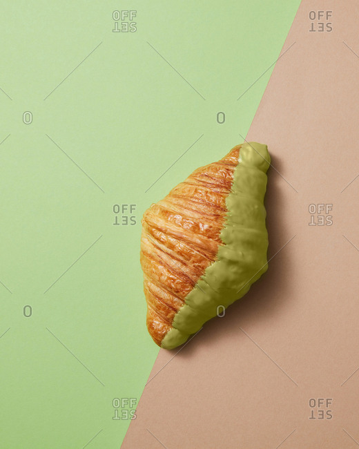 Close up view of homemade delicious French croissant with green sweet icing on a duotone green beige background. Copy space. Concept of breakfast continental.