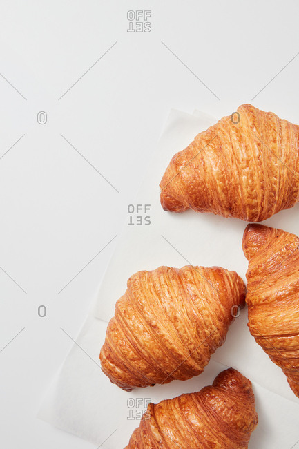 Top view of fresh homemade tasty baked goods, crispy French croissants on a gray background with place for text. Concept of continental breakfast.