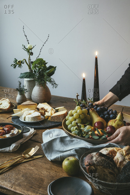 Woman placing food for dinner party on rustic table