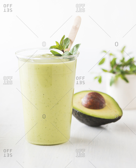 Avocado smoothie in clear glass with avocado behind