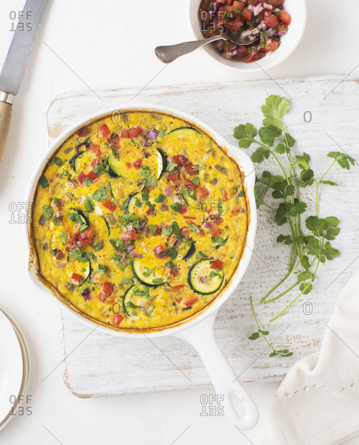 Vegetable frittata in skillet overhead with herbs