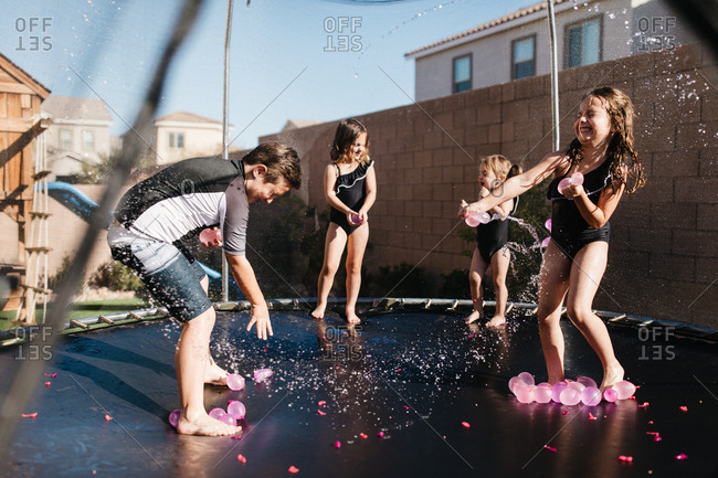 Kids having a water balloon fight with pink balloons on a trampoline