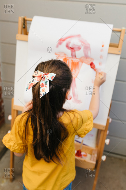 Rear view of a young girl painting a picture