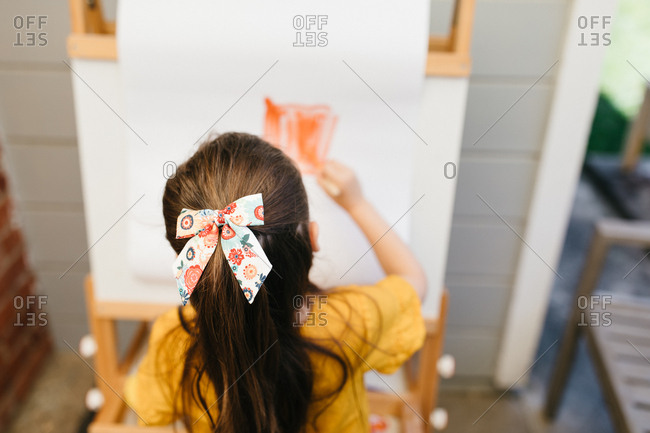 Young girl painting a picture from behind