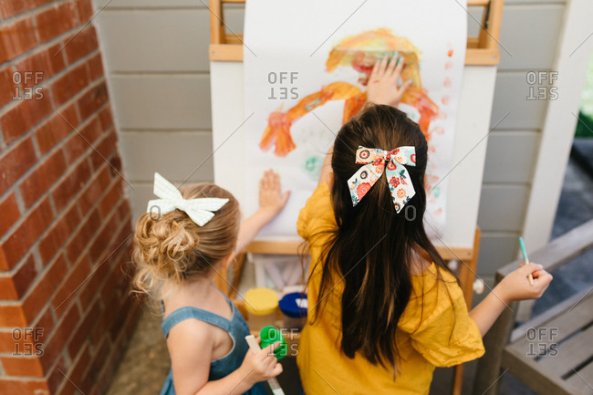 Two young girls painting a picture