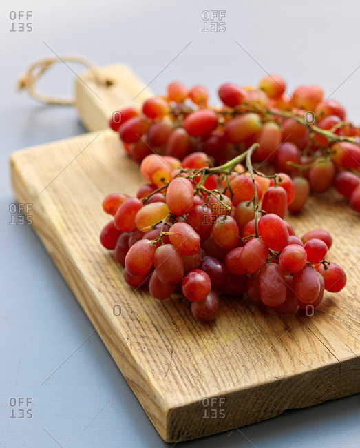 Red grapes on wooden board