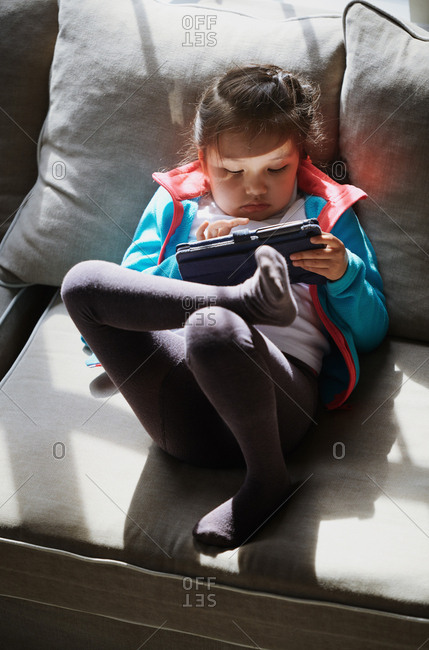 Cute girl sitting on the couch and using tablet computer