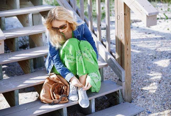 Blond woman tying shoelaces while sitting on the beach staircase