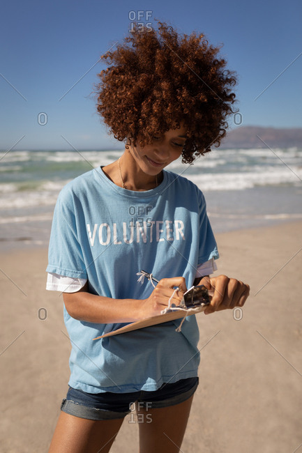 Portrait of young mixed race woman writing on clipboard at beach on a sunny day