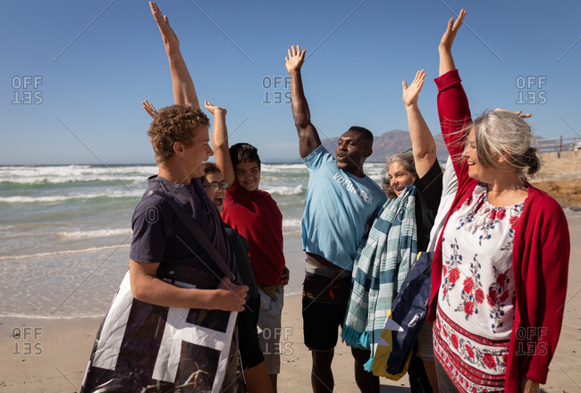 Front view of multi ethnic group of Volunteers forming hand stack on the beach