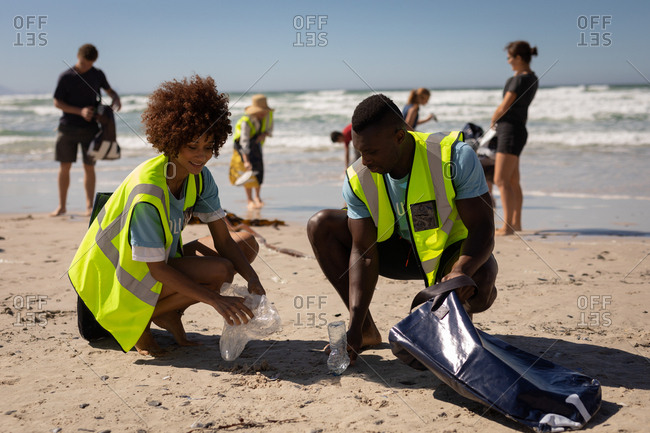 Front view of multi ethnic volunteers cleaning beach on a sunny day