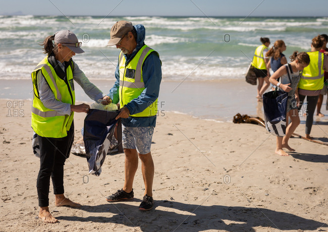 Front view of a group of multi ethnic volunteers cleaning beach on a sunny day