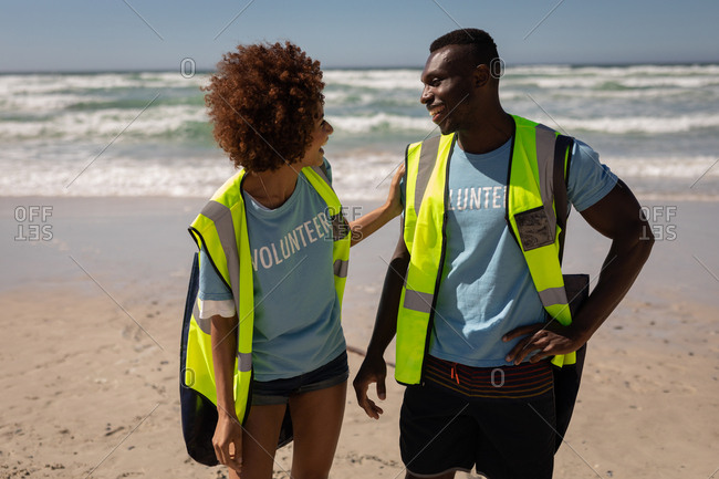 Front view of two happy multi ethnic volunteers interacting with each other on the beach