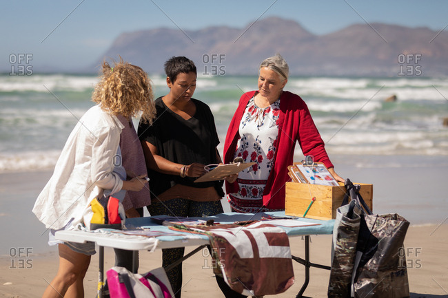 Front view of multi ethnic female volunteers discussing over clipboard while standing behind table on the beach