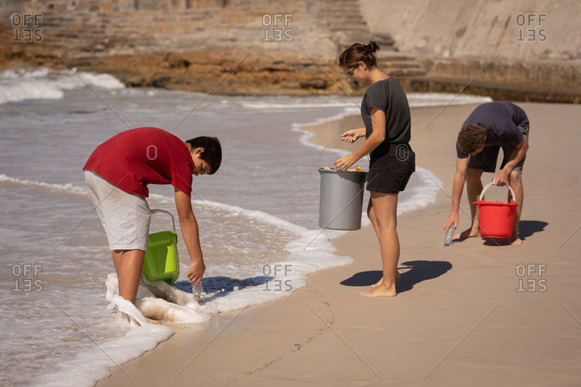 Front view of group of multi ethnic volunteers cleaning beach with buckets in their hands on a sunny day