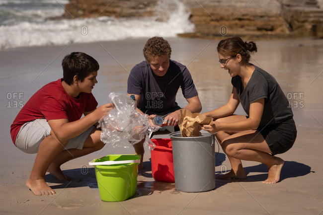 Front view of group of multi ethnic volunteers cleaning beach while sitting in squat position in front of buckets on a sunny day