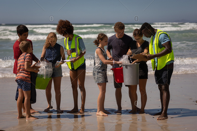 Front view of young group of multi ethnic volunteers cleaning beach on a sunny day