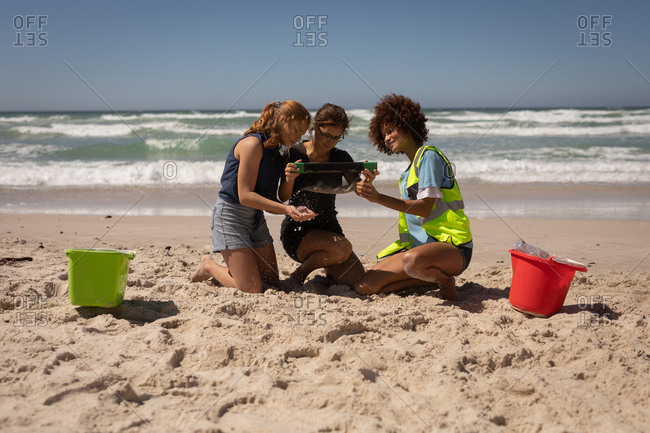 Front view of group of multi ethnic volunteers sitting on their knees to clean the beach on a sunny day