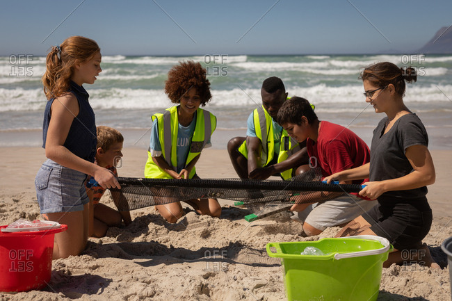 Front view of group of multi ethnic volunteers finding waste with a net while sitting on the knees at beach on a sunny day