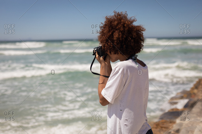 Side view of young mixed race woman clicking photos with digital camera at beach on a sunny day