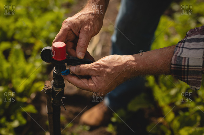 Close-up view of senior Caucasian male farmer repairing valve pipe in farm on a sunny day