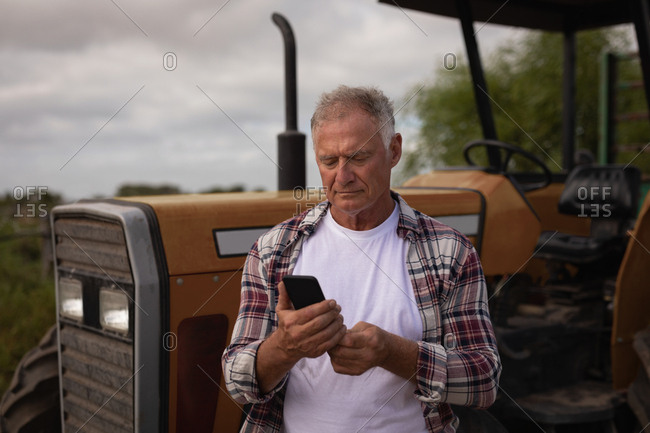 Front view of senior Caucasian male farmer using mobile phone while standing in front of his tractor in farm