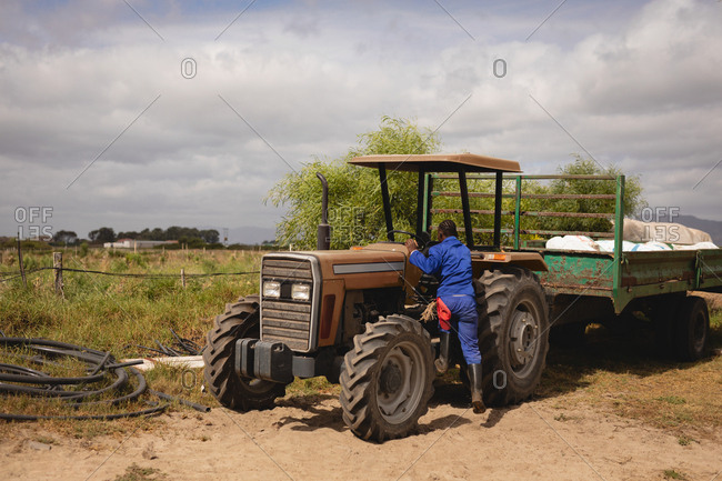 Rear view of African-American male farmer in coverall getting on tractor on farm road