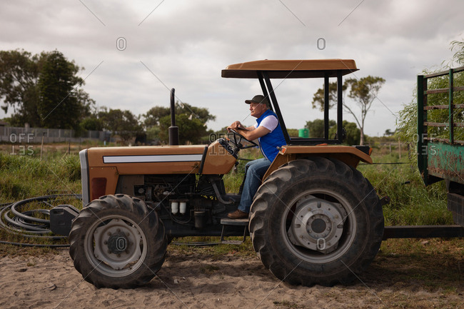 Side view of a senior Caucasian male farmer driving tractor on farm road