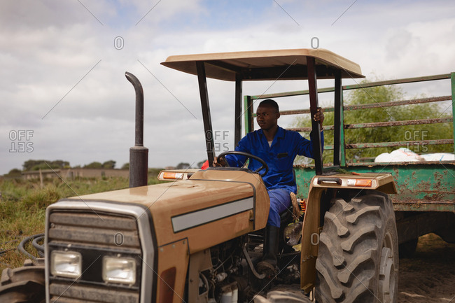 Front view of African-American farmer driving tractor with green trailer on farm